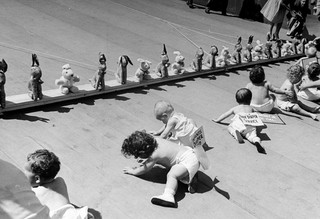 Babies crawling toward a mobile row of stuffed animals during the 1946 Diaper Service Derby. Photo by Cornell Capa / Getty Images