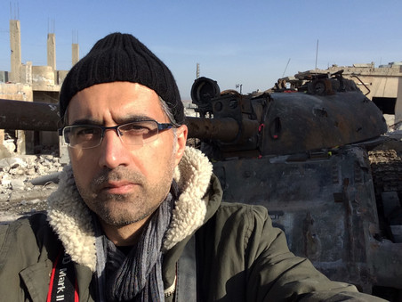 Selfie of filmmaker Reber Dosky in Kobani, in front of a tank captured by ISIS.