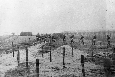 Soldiers make their way across a series of barbed wire defenses in WWI, c. 1915. Photo by Getty Images