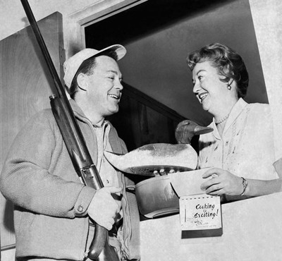 An unsuccessful duck hunter hands his wife a decoy and a cookbook for preparing it. Photo by Underwood Archives / Getty Images
